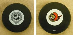 LOT OF 2 HOCKEY PUCKS -NHL OFFICIAL IN GLAS CO - OTTAWA SENA